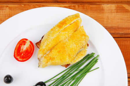 served fish fillet with greek olives,tomatoes,chives and lemon on white plate over wood Stock Photo - 14314748