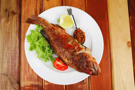 main course : roasted sea fish on plate with tomatoes, lemon and spices photo
