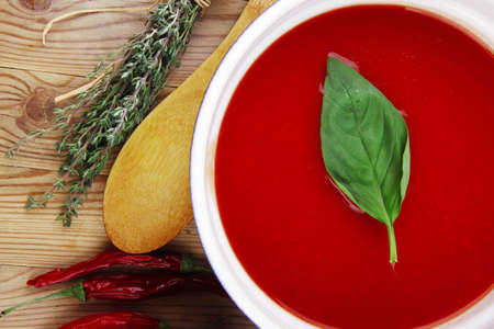 hot fresh diet tomato soup with basil thyme and dry pepper in big bowl on wood table photo