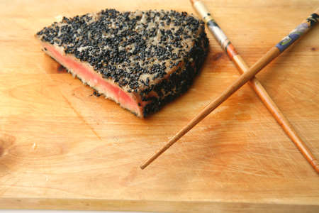 grilled tuna piece with black sesame on wooden plate and wooden chopsticks isolated on white photo