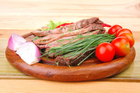 beef slices on plate with vegetables over wooden table photo