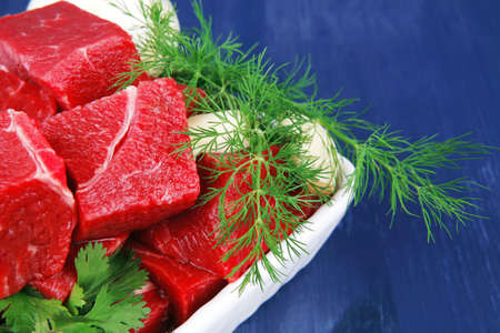 fresh uncooked beef meat slices over white bowls ready to prepare with green hot peppers and greenery serving over blue wooden table photo