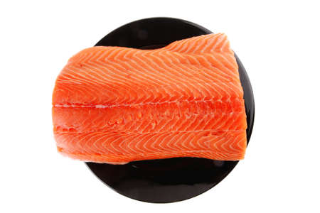 fresh uncooked red fish fillet on black over white photo