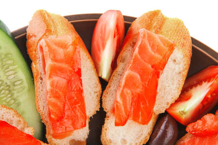 small salmon sandwiches served with vegetables photo