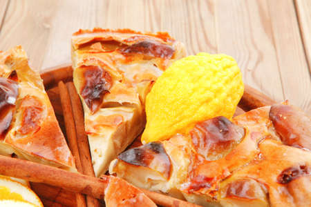 sweet food : cuts of apple pie on wooden plate with cinnamon sticks and lemons photo