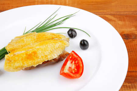 savory: fish fillet served on plate over wood with tomatoes,olives and bread Stock Photo - 14400915
