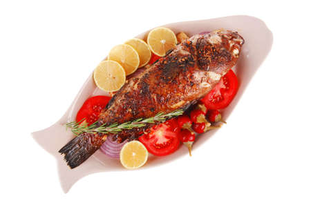main course: whole fryed sunfish on plate with lemons and peppers Stock Photo - 14400909