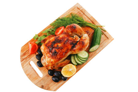baked meat : fresh whole chicken with black olives and raw tomatoes on wooden board isolated over white background photo