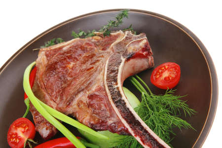 savory : roasted beef spare rib on dark dish with cutlery thyme pepper and tomato isolated over white background photo