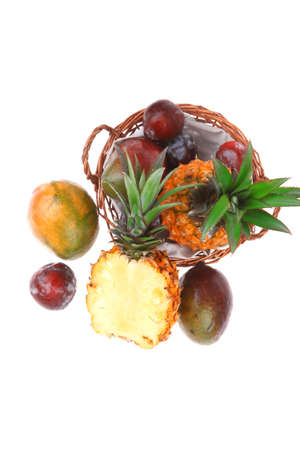 diet food - set of lot of tropical fruits include pineapple plum and mango in small basket isolated over white background photo