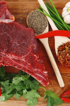 uncooked meat : raw fresh beef pork rib ready to cooking with garlic and red hot pepper over wood isolated over white background photo