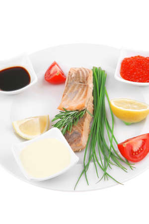 healthy fish cuisine : grilled pink salmon steaks with red caviar lime and sauces on white dish isolated over white background photo