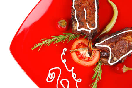 served entree: ribs on red plate with hot peppers and tomatoes photo