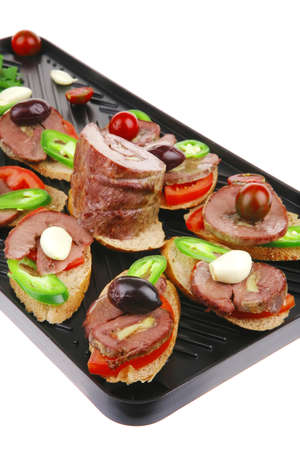 snakes on grill plate : tartlets with sliced meat and supplements isolated over white background photo