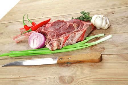 fresh meat : raw beef spare ribs with thyme , garlic and red chili pepper over wooden table photo