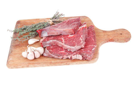 raw beef meat fillet with peppercorn and thyme ready to grill on wood figured aged board isolated over white background photo
