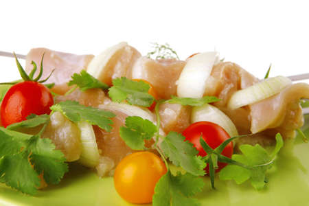 served uncooked chicken kebabs with raw vegetables photo