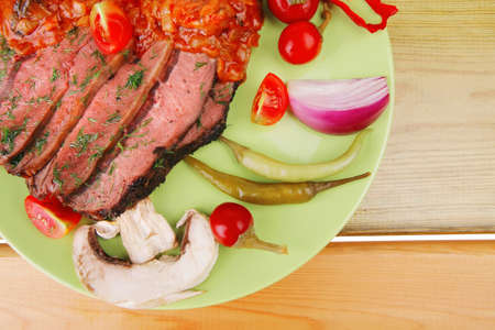 beef on plate with peppers over wooden table photo