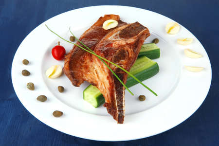 hot red beef meat steak on white plate with capers and tomatoes on blue wooden table photo
