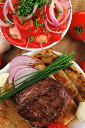 roast meat : beef ( lamb ) steak garnished with onion , tomatoes salad and chives, on wooden table photo