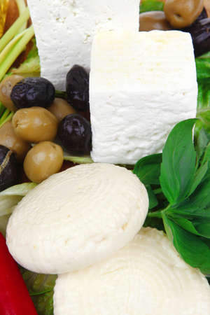 diet food : greek feta white cheese served on wooden plate with basil leaves red hot pepper , black and green olives , and olive oil isolated over white background photo