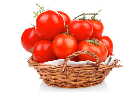 vegetable basket: fresh tomatoes on green branch in wicker basket isolated on white background