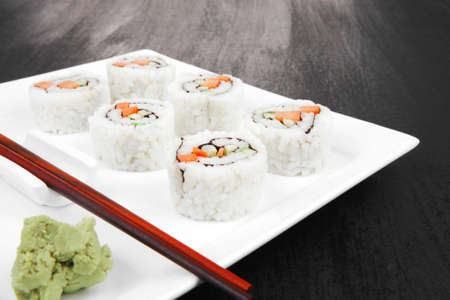Japanese Cuisine - California Roll with Cucumber , Cream Cheese and Raw Salmon inside. Served with wasabi . over black table . on square white plate photo