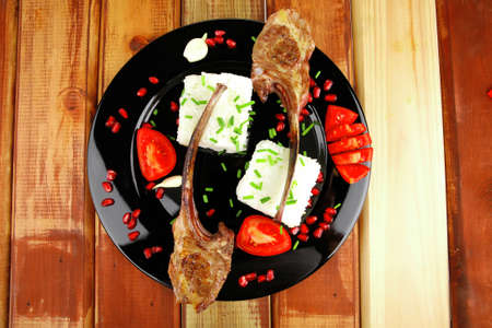 meat portion: barbecued ribs served with rice and tomatoes on black over wood photo