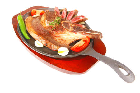 fresh roasted beef meat bone steak on metal iron plate with red hot pepper and tomatoes isolated on white background photo