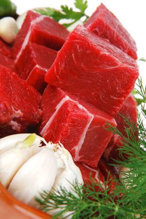 セラミック ボールの白い背景で隔離の緑とニンニクを準備する準備ができて上新鮮な未調理の牛肉をスライスします。