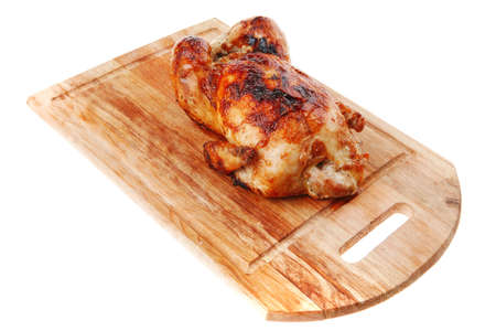 poultry : fresh grilled whole chicken on wooden cutting board isolated over white background photo