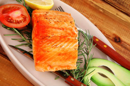 healthy food: hot baked salmon piece served over glass plate on wood photo