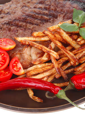 main course : grill beef steak with potato chips and fresh cherry tomato , red hot chili peppers on plate isolated on white background photo