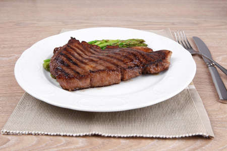 meat table : grilled beef fillet with asparagus served on white plate with cutlery over wooden table photo