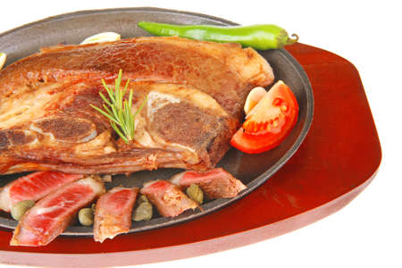 red beef meat steak on metal iron plate with green hot pepper and tomatoes isolated on white background photo