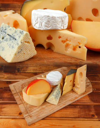different cheeses served on wooding cutting board Stock Photo