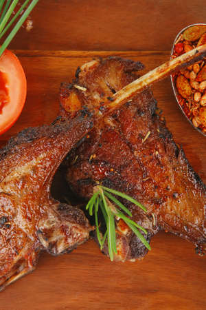 savory plate on wood : grilled ribs on plate with chives and tomato isolated on white background photo