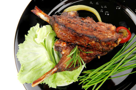 meat savory: roast ribs on black plate with peppers and chives photo