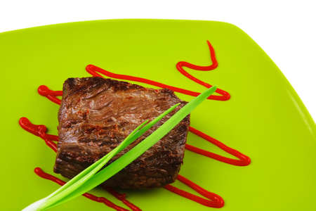 meat savory : grilled beef fillet mignon on green plate with chives and ketchup isolated over white background photo