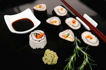 soysauce: Roll with Cucumber , Cream Cheese with raw Tuna and Salmon inside. on black wooden plate. Japanese traditional Cuisine Stock Photo
