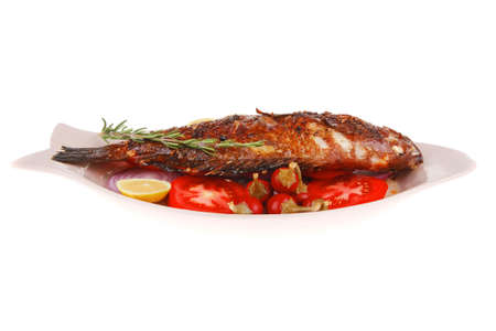 whole fried bass on plate, served with lemons and tomatoes Stock Photo - 14783001