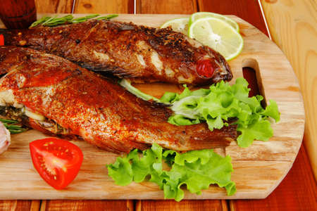 castors: savory on wooden table: two fried fish served with tomatoes and castors