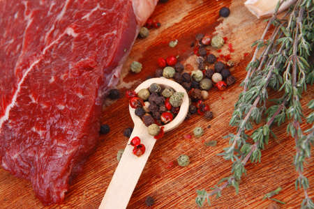 fresh raw beef meat fillet flesh with peppercorn and thyme ready to grill on wood board isolated over white background photo