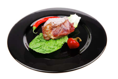 meat food : roast beef garnished with green lettuce and red chili hot pepper on black dish isolated over white background photo