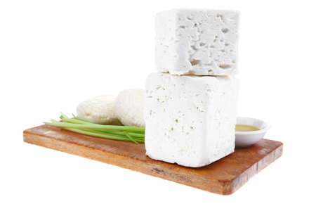 dairy product : raw soft mediterranean feta white cheese cubes and round on wooden plate isolated over white background photo