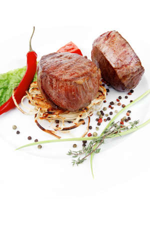 grilled beef fillet medallions with thyme and red hot chili pepper on plate isolated over white background