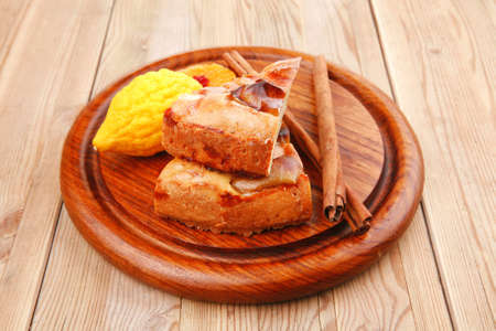 sweet apple cake with lemon and cinnamon sticks on wooden table photo