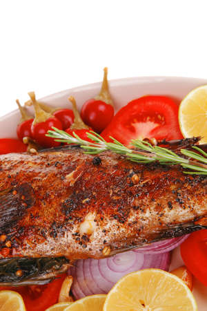 whole fried bass on plate, served with lemons and tomatoes Stock Photo - 14787517