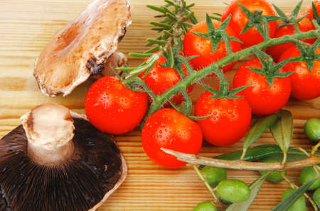 fresh raw vegetables on wooden board over white photo
