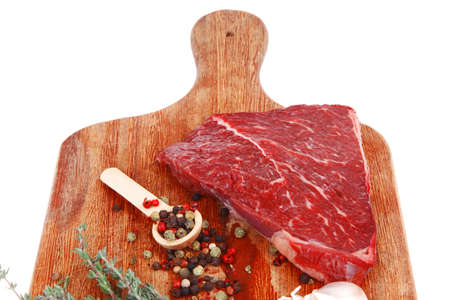 raw beef meat fillet with peppercorn and thyme ready to grill on wood board isolated over white background photo